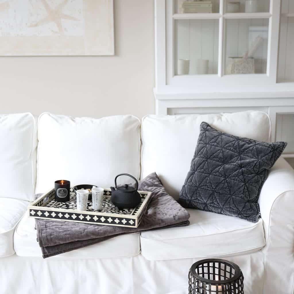 Einrichtung mit weißem Schrank, einem weißen Sofa und dunklen Akzenten in Naturmaterialien